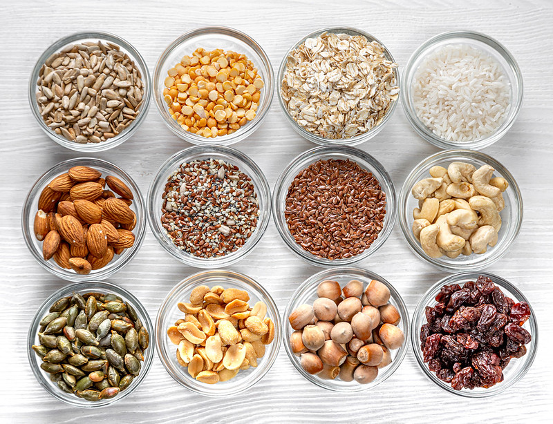 Seeds, nuts, grains in glass bowls on a white wooden background.