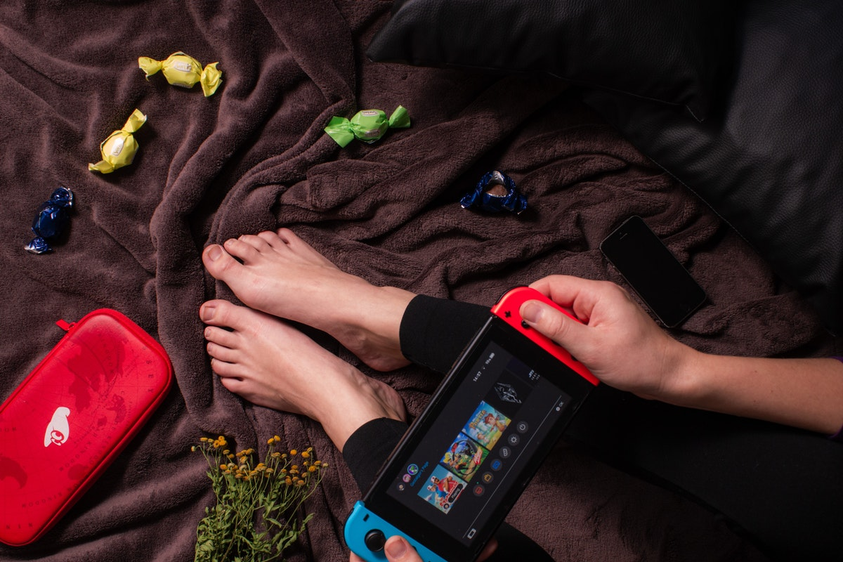A person holding a Nintendo Switch on their legs, sitting on a bedspread with candy strewn about.