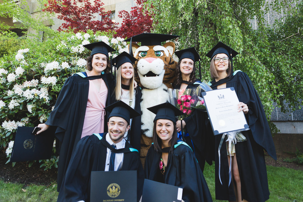 A group of graduating students with a Tiger mascot.