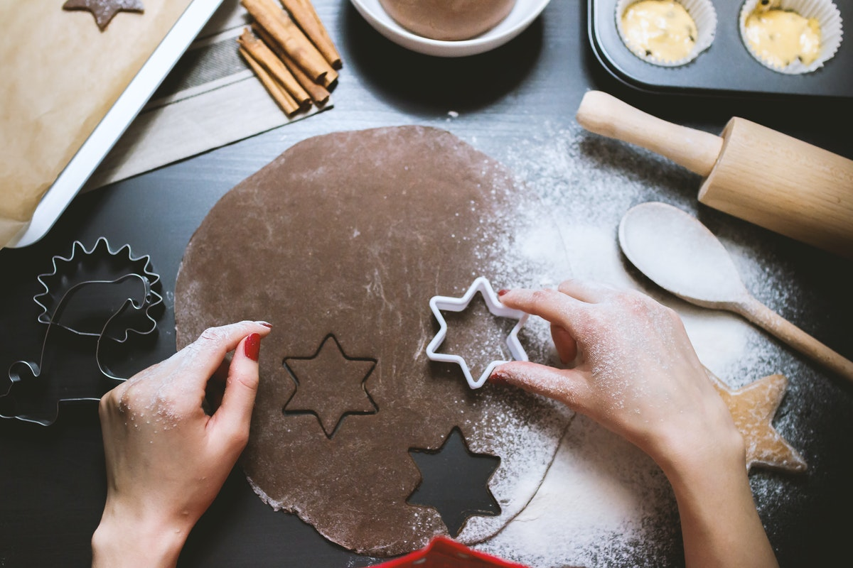 A girl presses a star-shaped cookie cutter onto dough.