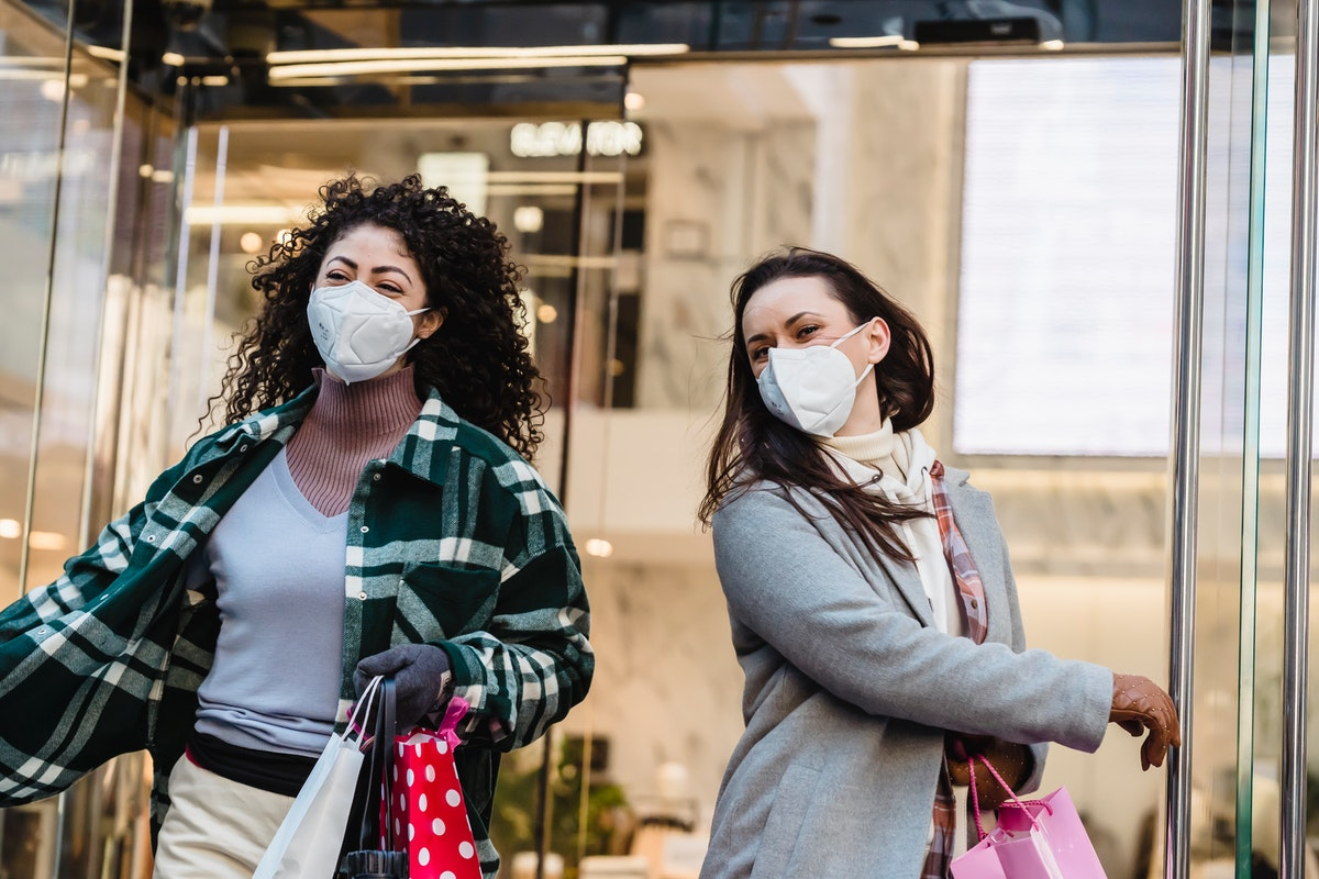 Two women wearing face masks and holding shopping bags exit a store.