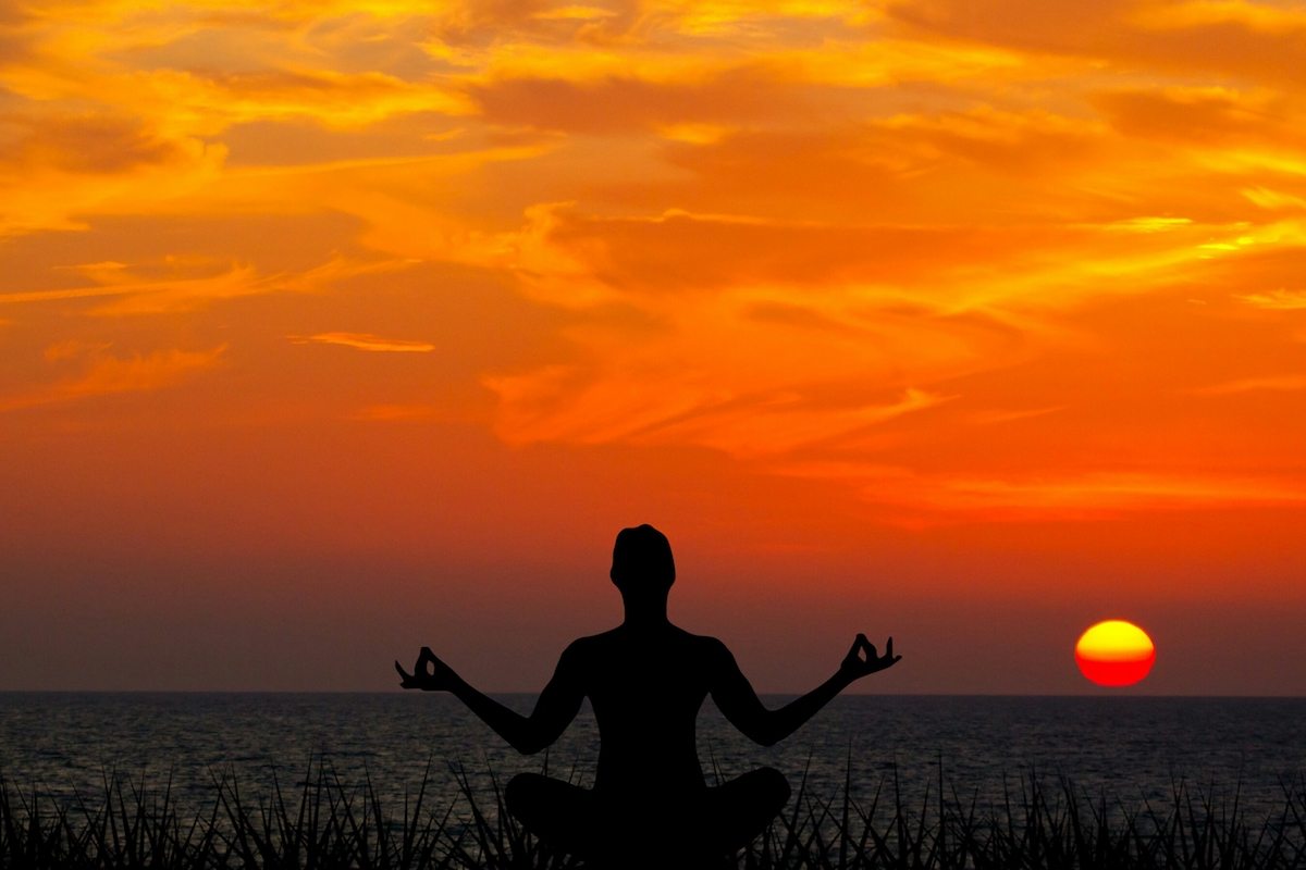 Person meditating in front of a sunset